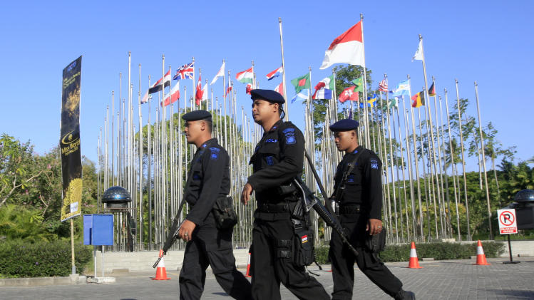 Indonesian police officers patrol around the venue of the Miss World competition in Nusa Dua, Bali, Indonesia, Saturday, Sept. 28, 2013. The Miss World final will be held later in the day after weeks of protests from Muslim hardliners and warnings that extremists could attack the pageant. (AP Photo/Firdia Lisnawati)