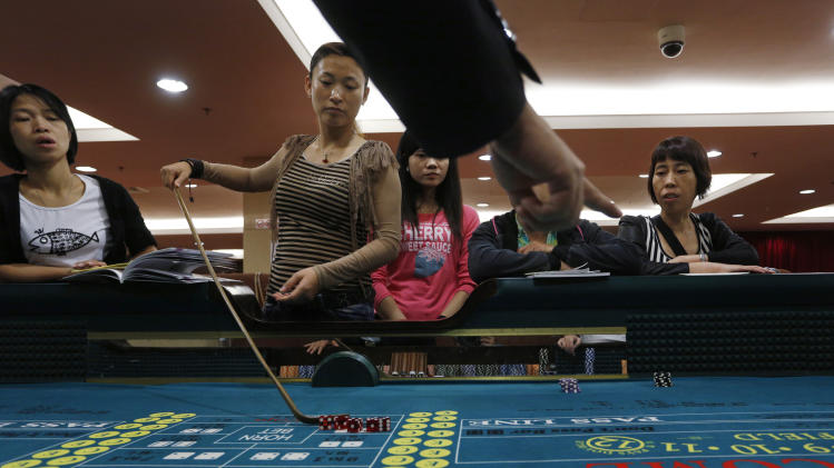 In this Oct. 25, 2012 photo, a gambling school students take a practice on a tabel in Macau, China. Hordes of Chinese high rollers flooding into Macau have turned the city into an Asian casino boomtown but they're also posing a challenge for China's next generation of leaders.(AP Photo/Vincent Yu)