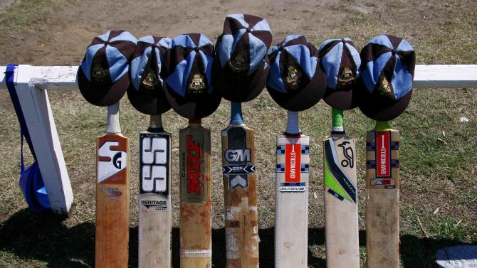 Cricket bats with caps placed on top can be seen resting on the boundary fence as a tribute to Australian cricketer Phillip Hughes, who died on Thursday, during a schoolboy's cricket match at Centennial Park in Sydney