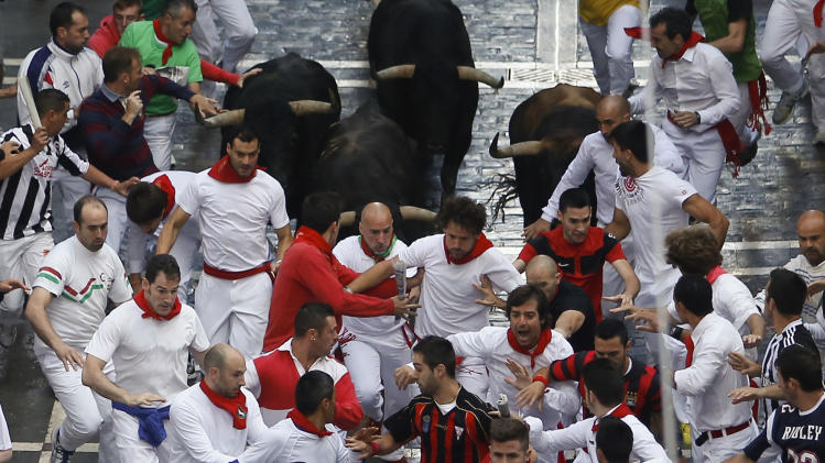Jandilla fighting bulls run after revelers during the running of the bulls at the San Fermin festival, in Pamplona, Spain, Friday July 11, 2014. Revelers from around the world arrive to Pamplona every year to take part in some of the eight days of the running of the bulls. (AP Photo/Andres Kudacki)