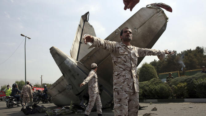 Iranian Revolutionary Guards prevent the media from approaching the wreckage of a passenger plane crash near the capital Tehran, Iran, Sunday, Aug. 10, 2014. An Iranian passenger plane crashed Sunday while taking off from an airport near the capital, Tehran, killing tens of people onboard, state media reported. (AP Photo/Vahid Salemi)