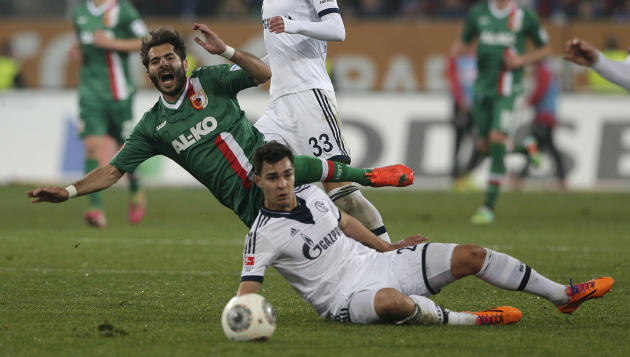 Augsburg's Halil Altintop of Turkey, top, is fouled by Schalke's Kaan Ayhan of Turkey challenge for the ball during the German first division Bundesliga soccer match between FC Augsburg and FC