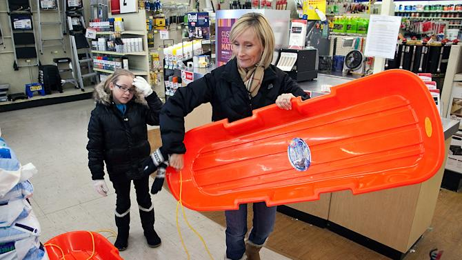 Tracy Damm and daughter Emily, 7, pick out a sled at Westlake Ace Hardware in Wichita, Kan., to enjoy for their first snow Wednesday, Feb. 20, 2013, since moving to Kansas from Texas. (AP Photo/The Wichita Eagle, Mike Hutmacher)
