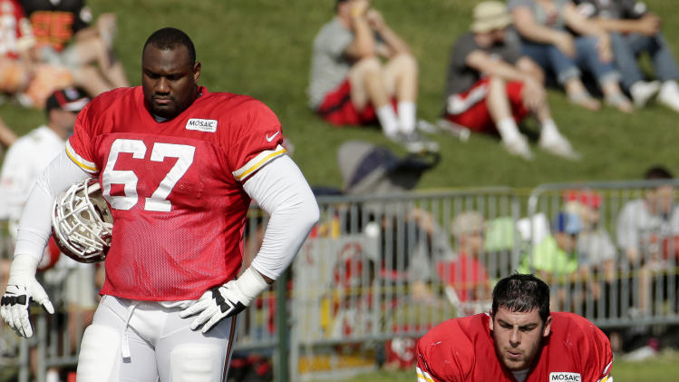 Kansas City Chiefs guard Otis Hudson (67) and offensive tackle Eric Fisher (72) watch a drill during NFL football training camp Monday, July 28, 2014, in St. Joseph, Mo. (AP Photo/Charlie Riedel)