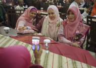 "In this Saturday, June 18, 2011 photo, Muslim people have their picture taken with a mobile phone during the launching ceremony of ""Klub Taat Suami,"" or ""Obedient to Husband Club,"" at a restaurant In Jakarta, Indonesia. The new club that aims to encourage women to be pious and totally obedient to their husbands has generated an outcry from some activists. (AP Photo/Dita Alangkara)"