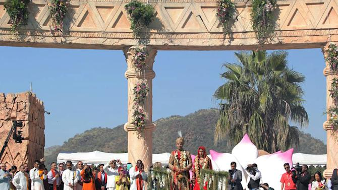 "In this photo supplied by The New Age newspaper of South Africa and taken Thursday May 2, 2013, guests watch as the bridal couple, Vega Gupta, centre right, and Aakash Jahajgarhia, are pulled across a pool on a float at Sun City's Palace of the Lost City, South Africa, during their wedding ceremony. The self-proclaimed ""wedding of the century"" has become a public relations disaster for the government since a private jet appears to have received diplomatic courtesies, allegedly bypassing customs procedures, when the jet landed the wedding party at the military Waterkloof Air Force Base near Pretoria, South Africa.  The jet landed Tuesday angering many South Africans who see the scandal as a case of cronyism linking big business and government and igniting accusations that security laws were breached. (AP Photo/The New Age)"