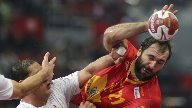 Canellas of Spain is blocked by Tej of Tunisia during the round of 16 match of the 24th men's handball World Championship in Doha