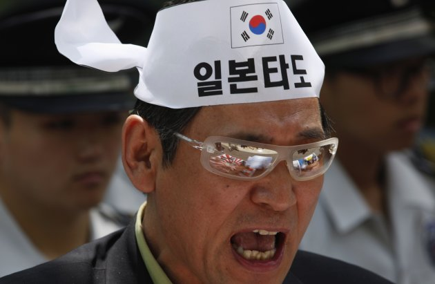 The rising sun flag is reflected in the glasses of an anti-Japan protester, in front of the official residence of the Japanese ambassador during a rally in Seoul
