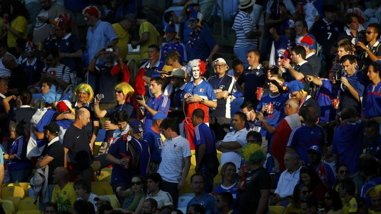Fans are illuminated by a ray of sunlight on the stands before the 2014 World Cup Group E soccer match between France and Ecuador at the Maracana stadium in Rio de Janeiro