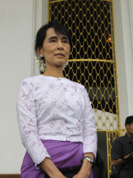 Myanmar's democracy icon Aung San Suu Kyi listens as Myanmar's Labor and Social Welfare Minister Aung Kyi, unseen, reads a statement nearby to the media after their meeting at Seinlekhanthar government guest house Friday, Aug.12, 2011, in Yangon, Myanmar. (AP Photo/Khin Maung Win)