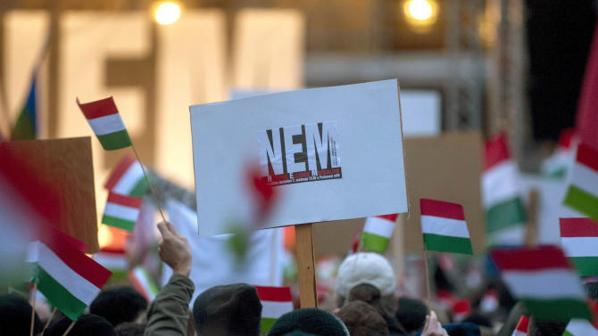 "Participants wave Hungarian national flags and hold a placard reading ""No"", as thousands of people attend a protest called Mass Demonstration Against Nazism in front of the Parliament building, unseen, in Budapest, Hungary, Sunday, Dec. 2, 2012. The protest has been provoked by MP of Jobbik party Marton Gyongyosi who demanded a list on Jewish Hungarians who are members of the Parliament or the government. (AP Photo/MTI, Janos Marjai)"