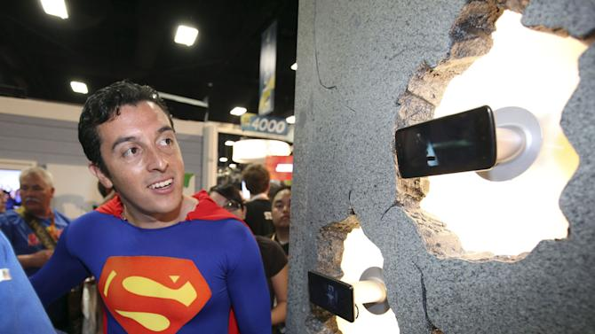 COMMERCIAL IMAGE - A fan of Superman discovers glasses-free 3D technology on LG Electronics mobile devices at the Legendary booth at Comic-Con on Friday July 13, 2012, at the Convention Center in San Diego. (Photo by Jeff Bottari/Invision for LG Mobile Phones/AP Images)