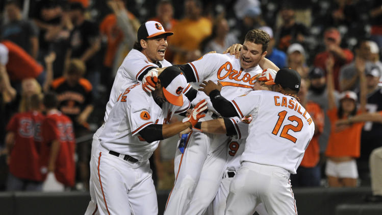 Baltimore Orioles Chris Davis, center, is picked up by teammates after driving in the game winning run against the Boston Red Sox in the 13th inning of a baseball game Thursday, June 13, 2013 in Baltimore. (AP Photo/Gail Burton)