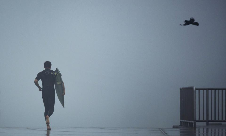 Surfers at Virginia Beach make their way through the early morning fog to catch some of the surf created by Tropical Storm Andrea in Virginia Beach, Va., Friday, June 7, 2013. (AP Photo/The Virginian-Pilot, L. Todd Spencer)