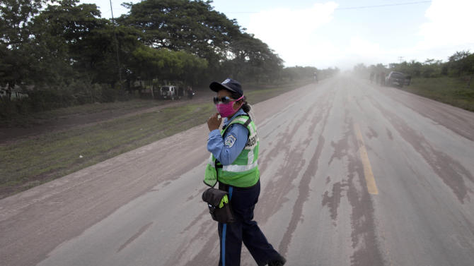 A Nicaraguan National Police officer patrols a road covered with volcanic ash spewed from the San Cristobal volcano, near Chinandega, Nicaragua, Saturday, Sept. 8, 2012. Nicaragua's tallest volcano, located about 70 miles (110 kilometers) northwest of Managua, near the Honduran border, has let off a series of explosions, spewing gases and showering ash on nearby towns, prompting an evacuations of residents. (AP Photo/Esteban Felix)