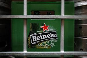 A plastic container with empty bottles of Heineken beers are pictured among beer kegs outside a restaurant in Singapore