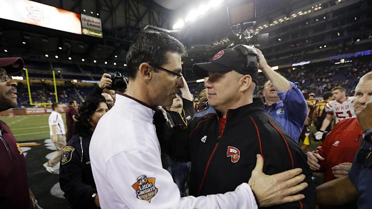 Western Kentucky interim head coach Lance Guidry, right, congratulates Central Michigan head coach Dan Enos, left, after their Little Caesars Pizza Bowl NCAA college football game at Ford Field in Detroit, Wednesday, Dec. 26, 2012. Central Michigan won 24-21. (AP Photo/Carlos Osorio)