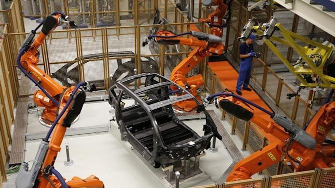 A worker makes technical measurements with robots on the carbon chassis at the serial production BMW i3 electric car in the BMW factory in Leipzig
