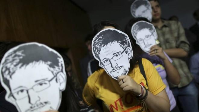 People wear Edward Snowden masks during Glenn Greenwald's testimony before a Brazilian congressional committee on Aug. 6.