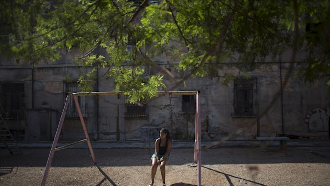 Social worker Stefani Gomes, 20, sits on a swing at a playground in Havana