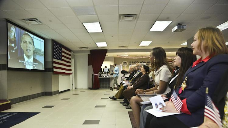 Immaculee Ilibagiza, third from right, and fellow immigrants from 16 countries, view a video message from President Obama during the U.S. Citizenship and Immigration Services   naturalization ceremony on Wednesday, April 17, 2013 in New York.  Ilibagiza sought asylum in the U.S. after fleeing the 1994 Rwandan genocide, which claimed more than 500,000 lives, became a U.S. citizen today.  (AP Photo/Bebeto Matthews)