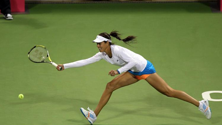 Ana Ivanovic of Serbia returns the ball to Daniela Hantuchova of Slovakia during the second day of the WTA Qatar Ladies Open in Doha, Qatar, Tuesday Feb. 11, 2014. (AP Photo/Osama Faisal)