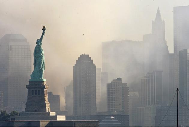 Smoke from the remains of New York's World Trade Center shrouds lower Manhattan as the Statue of Liberty stands in the foreground in this image taken across New York Harbor from Jersey City, New Jerse