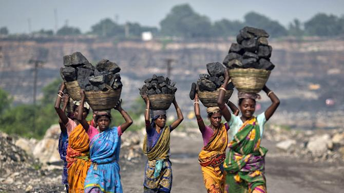 File photo shows local women carrying coal taken from an open cast coal field at Dhanbad district in Jharkhand