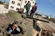 Syrian children play on a destroyed army tank in the northern Syrian town of Azaz. Explosions shook Damascus as warplanes launched their heaviest air raids yet and two car bombs struck on Monday, with the UN-Arab League peace envoy saying Syria's conflict was going from bad to worse