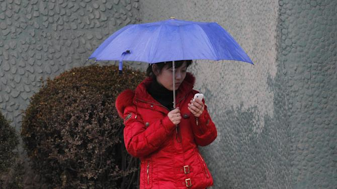 FILE - In this March 16, 2012 file photo, a North Korean woman uses a cellphone on a sidewalk in Pyongyang, North Korea. North Korea is loosening its restrictions on foreign cellphones and is allowing visitors to bring their own phones into the country. The policy reverses a longstanding rule requiring visitors to relinquish their foreign phones at the border. (AP Photo/Kim Kwang Hyon, File)