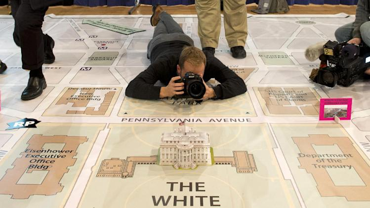 A news photographer takes photos of a model of the White House on a giant planning map during a media tour highlighting inaugural preparations being made by the Joint Task Force-National Capital Region for military and civilian planners , Wednesday, Dec. 12, 2012, at the DC Armory in Washington.  (AP Photo/ Evan Vucci)