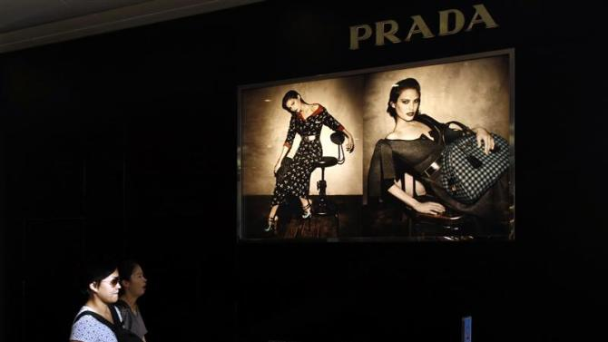 Shoppers walk past a Prada store at Hong Kong's shopping Tsim Sha Tsui district