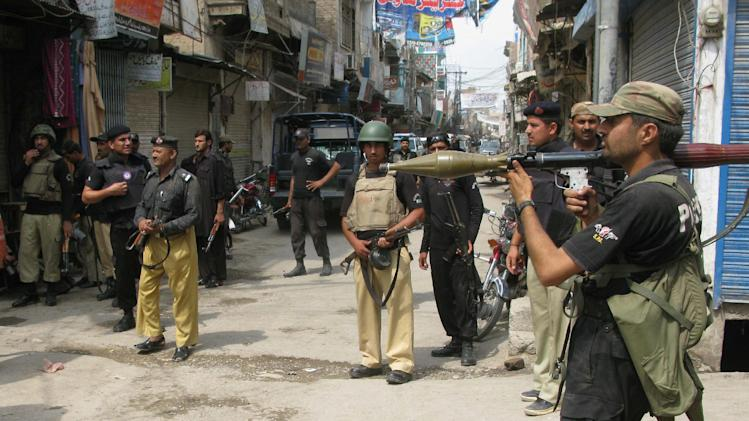 Pakistan's police commandos take positions near the security force's intelligence office in Bannu, Pakistan, Monday, July 16, 2012. The attack, claimed by the Pakistani Taliban, occurred in the militant stronghold of North Waziristan in the rugged tribal region near the border with Afghanistan Monday, where several hostages were taken before police stormed the building and ended the siege, police said. (AP Photo/Ijaz Mohammed)
