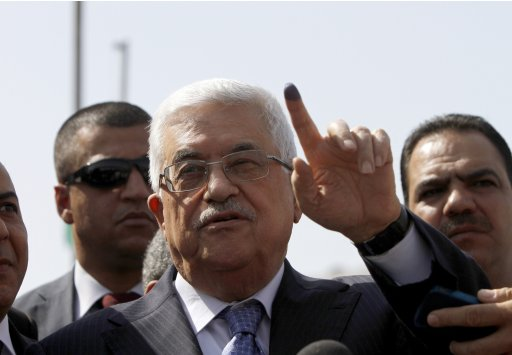 Palestinian President Abbas shows ink-stained finger while speaking to the media in Al-Bireh