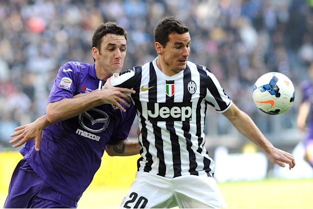 Juventus midfielder Simone Padoin, right, challenges for the ball with Fiorentina's Gonzalo Rodriguez during a Serie A soccer match between Juventus and Fiorentina at the Juventus stadium, in Turi