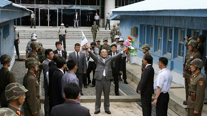 """Activist No Su-hui, center, shouts  """"Long Live Reunification""""  in front of North Korean officials and soldiers, foreground, before crossing the demarcation line between North and South Korea where South Korean officials, at rear, were waiting for him, at the Demilitarized Zone at Panmunjom, Korea, on Thursday, July 5, 2012. South Korean officials immediately detained the activist for making an extended trip to Pyongyang without South Korean government approval as required by law. (AP Photo/Kim Kwang Hyon)"""