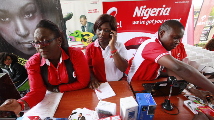 Staffs of Airtel attend to a customer during the launch of mobile number portability in Lagos, Nigeria, Monday, April 22, 2013. Mobile phone users in Nigeria can now keep their old number when switching services, a major shakeup in the West African nation's lucrative telecommunications market where customers often complain of poor service. The service, pushed by the federal Nigerian Communications Commission, began Monday across the nation of more than 160 million people. Under the service, customers can keep their number and can switch providers every 90 days for free. (AP Photo/Sunday Alamba)