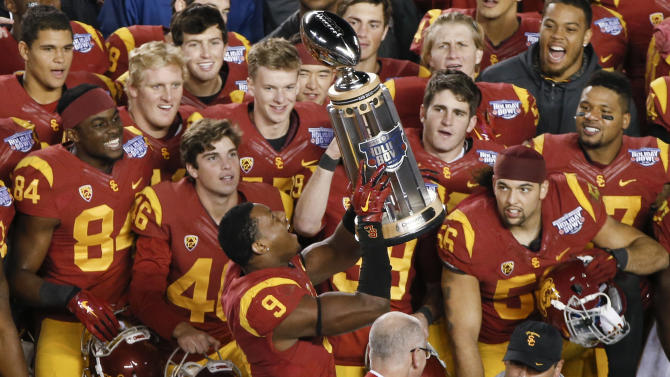 Southern California wide receiver JuJu Smith lifts the Holiday Bowl trophy after Southern California's 45-42 victory over Nebraska in the NCAA football game Saturday, Dec. 27, 2014, in San Diego. (AP Photo/Lenny Ignelzi)
