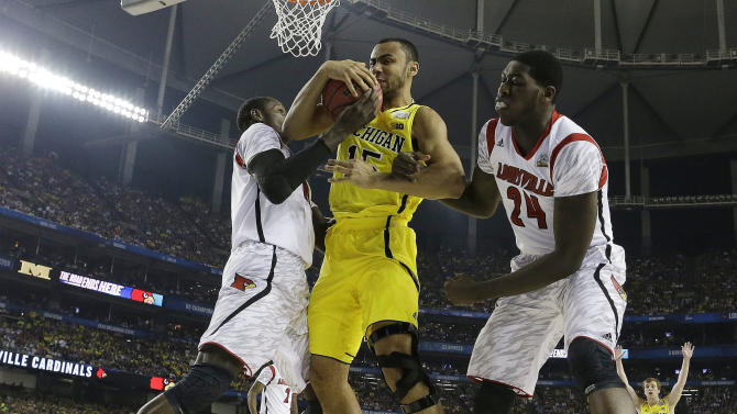 Michigan forward Jon Horford (15) and Louisville center Gorgui Dieng (10) and Louisville forward Montrezl Harrell (24) work for a rebound during the first half of the NCAA Final Four tournament college basketball championship game Monday, April 8, 2013, in Atlanta. (AP Photo/David J. Phillip)