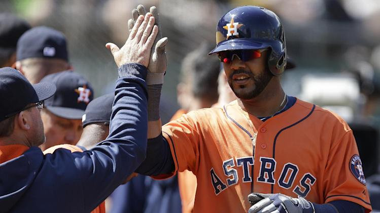 Houston Astros' Jonathan Villar, right, is congratulated after scoring against the Oakland Athletics in the fifth inning of a baseball game Saturday, April 19, 2014, in Oakland, Calif. Villar scored on a throwing error by A's catcher Derek Norris after Villar stole third base. (AP Photo/Ben Margot)