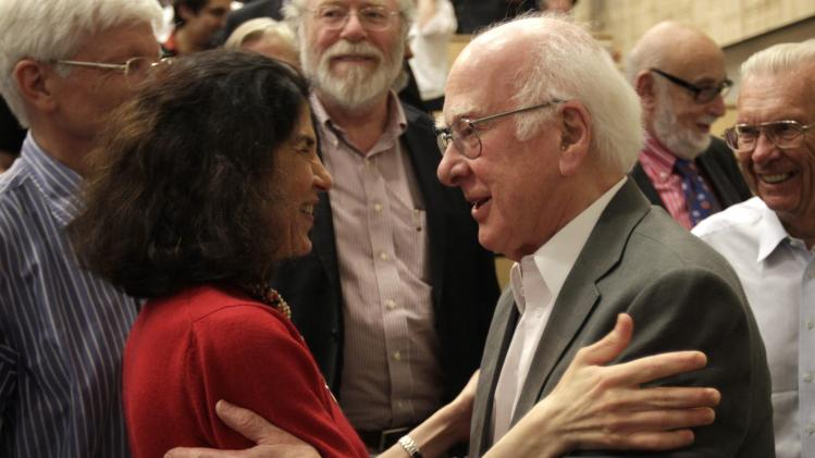"""British physicist Peter Higgs, right, congratulates Fabiola Gianotti, ATLAS experiment spokesperson, after her results presentation during a scientific seminar to deliver the latest update in the search for the Higgs boson at the European Organization for Nuclear Research (CERN) in Meyrin near Geneva, Switzerland, Wednesday, July 4, 2012. The head of the world's biggest atom smasher is claiming discovery of a new particle that he says is consistent with the long-sought Higgs boson known popularly as the """"God particle"""" which is believed to give all matter in the universe size and shape. (AP Photo/Denis Balibouse, Pool)"""