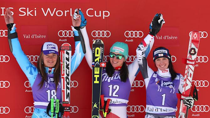Marianne Kaufmann-Abderhalden, center, winner of an alpine ski, women's World Cup downhill, celebrates on the podium with second placed Tina Maze, left, and third placed Cornelia Huetter, in Val D'Isere, France, Saturday, Dec. 21, 2013. Marianne Kaufmann-Abderhalden of Switzerland earned her first World Cup victory by winning a women's downhill on Saturday that was marked by a number of big crashes and Lindsey Vonn skiing out and then clutching her injured right knee in pain. (AP Photo/Giovanni Auletta)