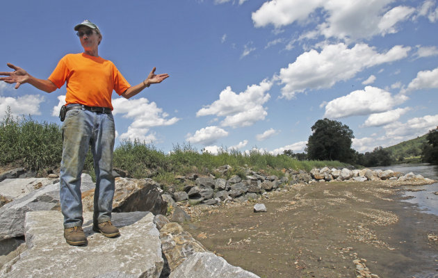 Doug Turner stands along the rebuilt river bank of the Mad River at his farm on Wednesday, Aug. 22, 2012 in Waitsfield, Vt. Devastating floods wrought by Hurricane Irene a year ago inundated farm fiel