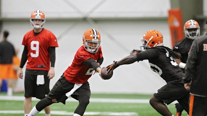 Cleveland Browns quarterback Johnny Manziel hands off during a rookie minicamp practice at the NFL football team's facility in Berea, Ohio Saturday, May 17, 2014. (AP Photo/Mark Duncan)