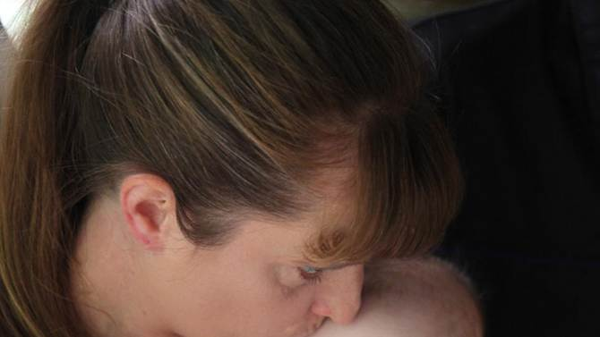 In this Sept. 16, 2011 photo, Kris Fallon kisses her 4-month-old daughter Addison, in Palatine, Ill. The Fallon family has been living in poverty for nearly two years. (AP Photo/Robert Ray)