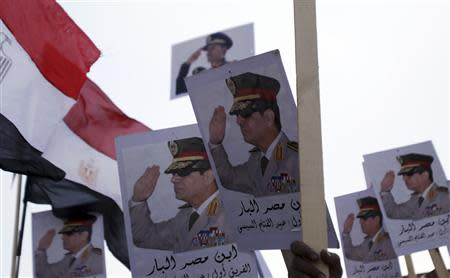 Posters of Army Chief Sisi are seen as supporters of the army protest against ousted Islamist President Mursi and members of the Muslim Brotherhood in Cairo