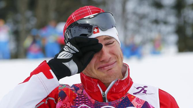 Winner Cologna of Switzerland reacts during the flower ceremony for the men's skiathlon event at the Sochi 2014 Winter Olympics in Rosa Khutor