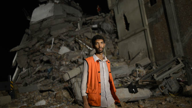 ADDS DATE -Saiful Islam Nasar poses in front of the rubble of a building collapse in Savar, near Dhaka, Bangladesh Monday April 29, 2013. Nasar, a mechanical engineer is one of hordes of volunteers who came to Savar to help with the rescue effort. They get no funding, have no training and buy their supplies themselves. They have featured largely in efforts to save those who were crushed in the worst disaster to hit Bangladesh's $20 billion a year garment industry.(AP Photo/Ismail Ferdous)