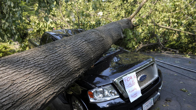 Mike Wolfe's pick-up truck lies under a fallen tree in front of his house  after a severe storm in Falls Church, Va., Saturday, June 30, 2012. Wolfe's daughter Samanth Wolfe created the for sale sign as a joke. (AP Photo/Cliff Owen)
