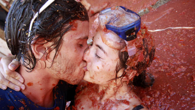 "Revelers  kiss each other during the annual ""Tomatina"" tomato fight fiesta in the village of Bunol, near Valencia, Spain, Wednesday, Aug. 29, 2012. Bunol's town hall estimated more than 40,000 people, some from as far away as Japan and Australia, took up arms Wednesday with 100 tons of tomatoes in the yearly food fight known as the 'Tomatina' now in its 64th year. (AP Photo/Alberto Saiz)"
